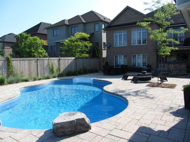 A backyard with a large, curvy shaped pool.