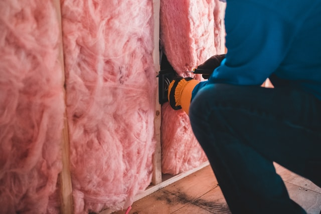 A man searching for a leak behind insulation.