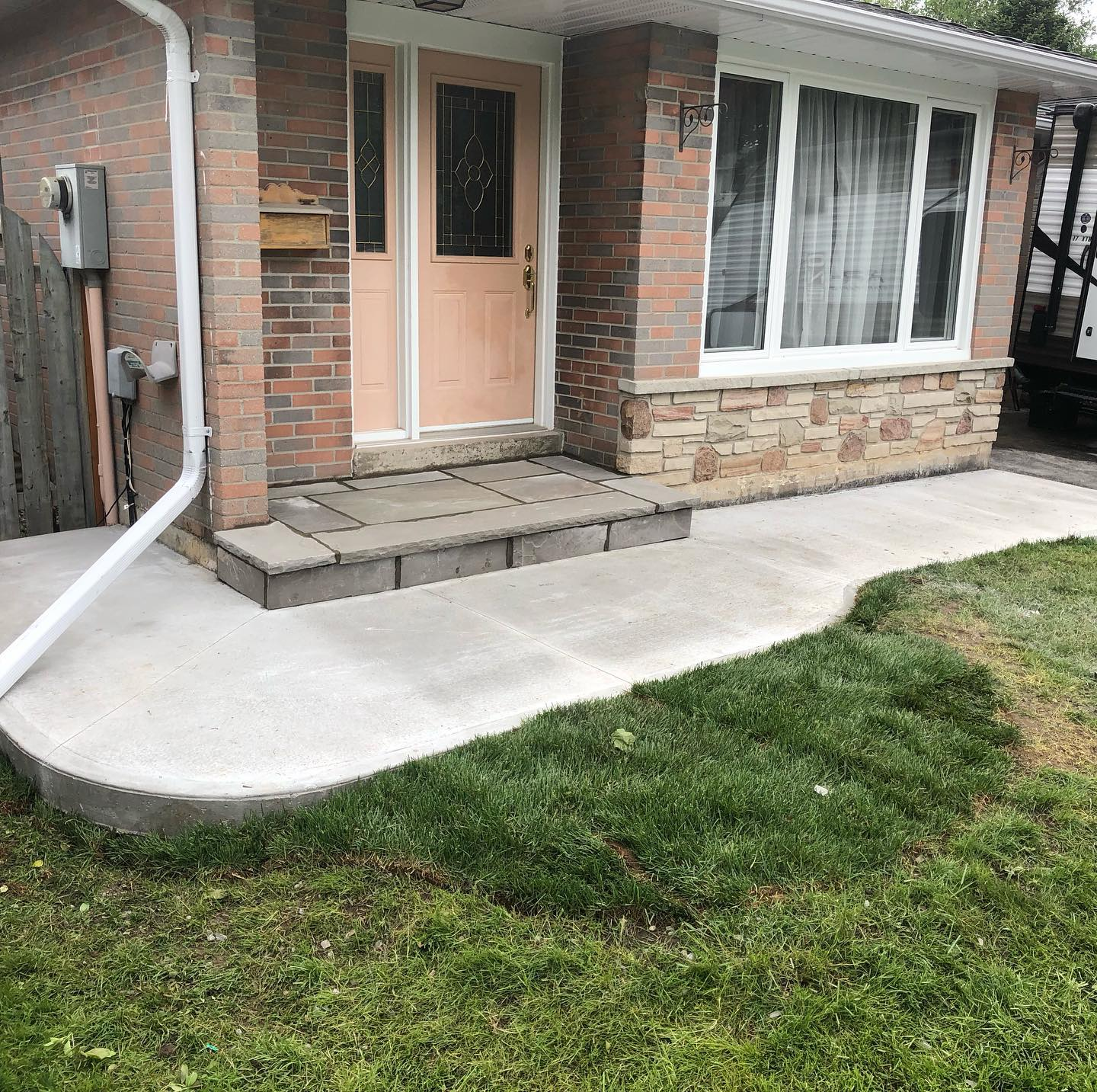 A walkway of concrete around the front of a house.