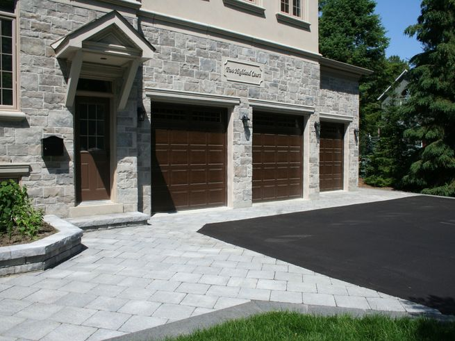 A paved driveway with two garage doors, and a patio walkway around the driveway.