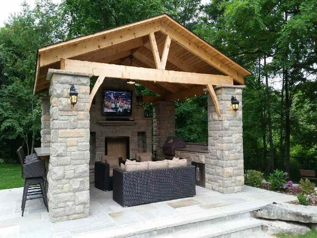 A gazebo with a tv and furniture inside.