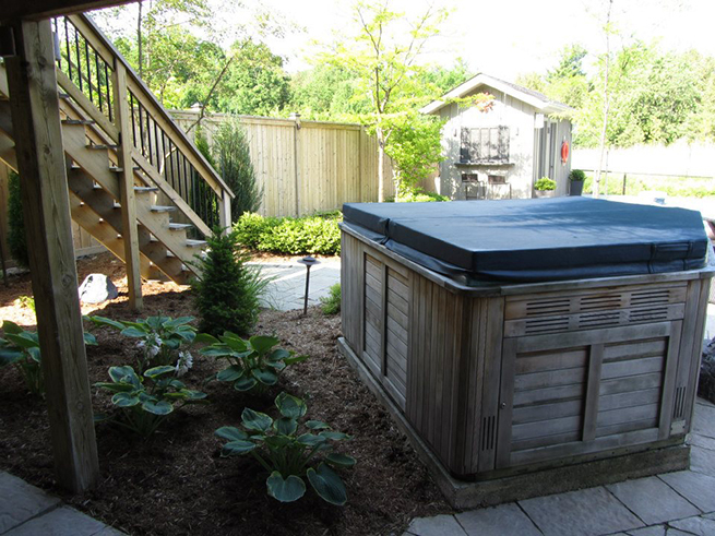 A backyard with a hottub and stairs.