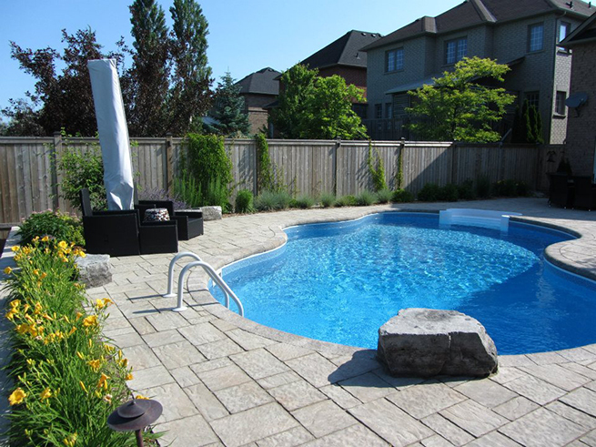Backyard with a pool, has ladder leading into it.