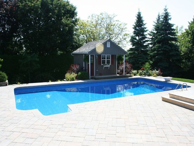 Rectangular shaped pool with shed.